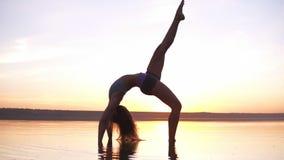 De jonge gezonde geschiktheidsvrouw die yoga doen, die zich in brug bevinden stelt Setu Bandhasana op de kust in het water bij zo stock video