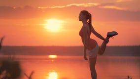 De jonge gezonde vrouw rekt haar spieren met een speciale oefening uit stock videobeelden