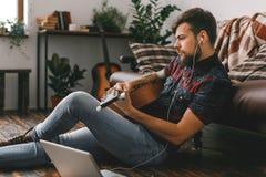 De jonge gitarist die hipster thuis op de de gitaar van de vloerholding het luisteren oortelefoons zitten klinkt stock foto's
