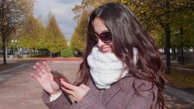 De jonge glimlachende donkerbruine vrouw met gekrulde lange haren in zonnebril gebruikt smartphone in stedelijk park stock footage