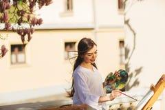 De jonge glimlachende donkerbruine vrouwenkunstenaar schildert een beeld op de straat, dichtbij een mooie boom van magnolia stock afbeelding