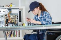 De jonge glimlachende donkerbruine vrouwentechnicus herstelt computer Royalty-vrije Stock Afbeeldingen