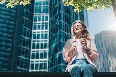 De jonge glimlachende hipster onderneemster in glazen zit in openlucht en houdend digitale tablet en kop van koffie royalty-vrije stock afbeelding