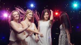 De jonge glimlachende meisjes dansen De stroboscooplampen verstrekken mooie verlichting stock videobeelden