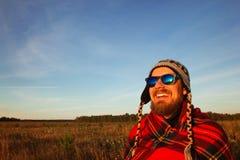 De jonge glimlachende mens in gebreide GLB, de zonnebril en de deken komt van zonsopgang op de achtergrond van een gebied en een  Stock Afbeelding