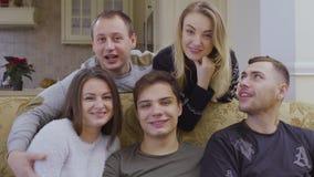 De jonge glimlachende mensen bekijken camera stock video