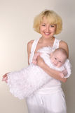 De jonge glimlachende moeder houdt haar baby in wapens Stock Afbeelding