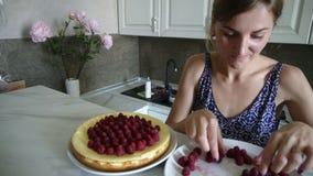 De jonge glimlachende vrouw aanbidt thuis en verfraait de bovenkant van de cake met frambozen in de keuken Een heerlijk dessert m stock footage