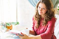 De jonge glimlachende vrouw drinkt koffie in een koffie Royalty-vrije Stock Fotografie