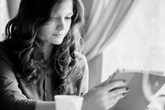 De jonge glimlachende vrouw drinkt koffie in een koffie Stock Afbeelding
