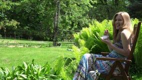 De jonge glimlachende vrouw eet roomijs in tuin 4K stock videobeelden