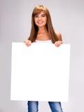 De jonge glimlachende vrouw houdt witte grote banner royalty-vrije stock afbeelding