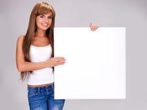 De jonge glimlachende vrouw houdt witte grote banner royalty-vrije stock afbeeldingen