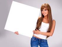 De jonge glimlachende vrouw houdt witte grote banner stock afbeelding