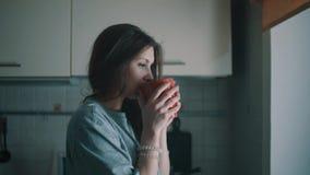 De jonge glimlachende vrouw kijkt in venster en drinkt koffie in keuken bij ochtend stock videobeelden