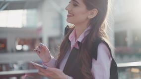 De jonge glimlachende vrouw met mooie samenstelling in het roze overhemd en het zwarte sleeveless jasje is in het winkelcentrum E stock video