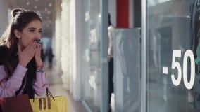 De jonge glimlachende vrouw met mooie samenstelling in het roze overhemd en het zwarte sleeveless jasje loopt in het winkelen stock videobeelden