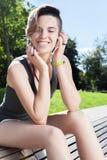 De jonge glimlachende vrouw rust op bank na jogging in park royalty-vrije stock fotografie