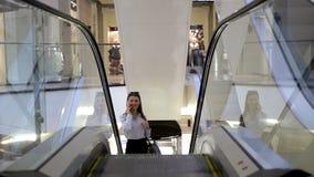De jonge glimlachende vrouw spreekt op haar celtelefoon in een wandelgalerij stock footage