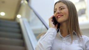 De jonge glimlachende vrouw spreekt op haar celtelefoon in een wandelgalerij stock videobeelden
