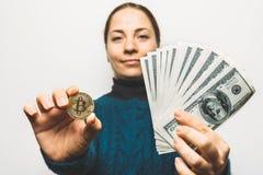 De jonge glimlachende vrouw toont Gouden Bitcoin-muntstuk - symbool van cryptocurrency, nieuwe virtuele geld en stapel dollarreke Royalty-vrije Stock Foto's