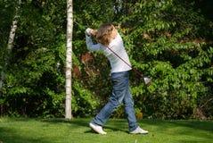 De jonge golfspeler voert een golfschot uit Stock Foto's