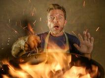 De jonge grappige en slordige mens van de huiskok met schort in de pan van de schokholding in brand die het voedsel in keukenramp stock foto's
