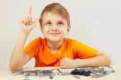 De jonge grappige ingenieur denkt dat van mechanische aannemer assembleert Stock Foto