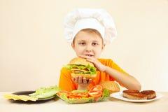 De jonge grappige jongen in chef-kokshoed geniet van kokend smakelijke hamburger Stock Foto