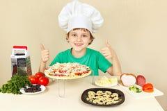 De jonge grappige jongen in chef-kokshoed geniet van kokend smakelijke pizza Royalty-vrije Stock Fotografie
