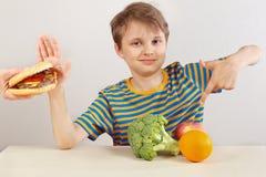 De jonge grappige jongen in een gestreept overhemd bij de lijst weigert hamburger ten gunste van fruit en groenten op witte achte royalty-vrije stock fotografie