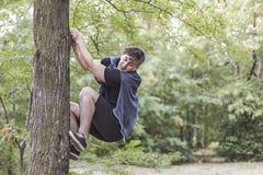 De jonge grappige Kaukasische mens beklimt tot de boom met hieronder markt of verschrikking van iets Witte draadloze oortelefoons stock afbeelding