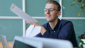 De jonge Grappige Luie Slechte Arbeider maakt een Document Vliegtuig in Bureau 4K stock footage