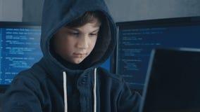 De jonge de hakkerprogrammeur van de wonderjongen in kap die bij de computer in het datacentrum werken vulde met de vertoningssch stock videobeelden