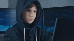 De jonge de hakkerprogrammeur van de wonderjongen in kap die bij de computer in het datacentrum werken vulde met de vertoningssch stock footage