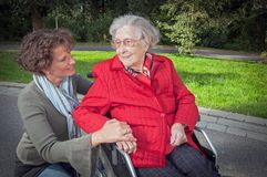 De jonge hand van de vrouwenholding van oude damezitting in rolstoel stock afbeelding