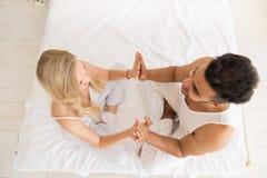 De jonge Handen die van de Paargreep in Bed, de Gelukkige Glimlach Spaanse Mens en Mening van de Vrouwen de Hoogste Hoek zitten Royalty-vrije Stock Afbeeldingen