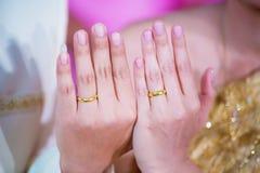 De jonge handen van de echtpaarholding, tonen trouwring in de dag van het ceremoniehuwelijk Stock Foto's