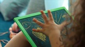 De jonge handen van de kunstenaar, weinig kindkunstenaar schildert een canvas met grafietpotloden, zittend een lijst en trekken o stock videobeelden