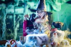 De jonge Heks kookt met Magisch Stock Foto