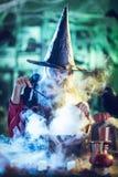 De jonge Heks kookt met Magisch Stock Foto's