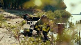 De jonge hengel die van de vissersholding op beet in de zomerdag wachten stock videobeelden