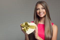 De jonge het glimlachen gift van de vrouwenholding De dag van de valentijnskaart stock afbeelding