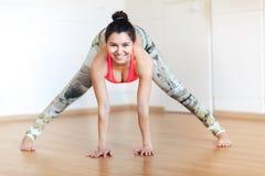 De jonge het glimlachen vrouw het praktizeren yoga, Ardha Padmasana stelt, mudra, het uitwerken Stock Fotografie