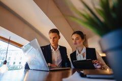 De jonge het zakenliedenjongen en meisje werken met laptop, een tablet en nota's in de koffie stock foto's
