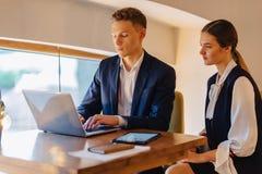 De jonge het zakenliedenjongen en meisje werken met laptop, een tablet en nota's in de koffie royalty-vrije stock foto's