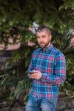 De jonge hipstermens houdt telefoon en het babbelen royalty-vrije stock afbeelding