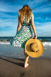 De jonge hoed van de vrouwenholding en het lopen op strandzand aan de oceaan Stock Afbeeldingen