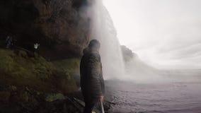 De jonge holding van de toeristenmens selfie plakt en schietend op de krachtige waterval Seljalandsfoss van de goprocamera in IJs stock video
