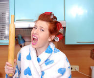 De jonge huisvrouw in haarkrulspelden in woede schreeuwt en bedreigt een deegrol bedreigd te hebben Stock Foto's